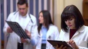 Een vrouwelijke arts houdt een tablet in haar handen Op de achtergrond, inspecteren de artsen de röntgenstraal stock footage