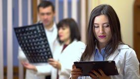 Een vrouwelijke arts houdt een tablet in haar handen Op de achtergrond, inspecteren de artsen de röntgenstraal stock video