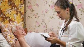 Een vrouwelijke arts ondervraagt thuis een patiënt Zij schrijft een anamnese aan de tabletcomputer stock video