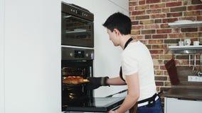 Een vrouwelijke bakker neemt heet brood uit de oven stock videobeelden