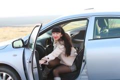 Een vrouwelijke bestuurder opent een autodeur royalty-vrije stock fotografie
