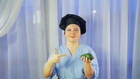 Een vrouwelijke chef-kok glimlacht, houdt een avocado in haar hand en richt aan het stock footage