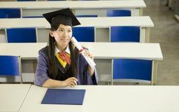 Een vrouwelijke gediplomeerde in klaslokaal Stock Afbeelding