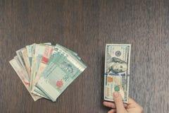 Een vrouwelijke hand die een honderd Amerikaanse dollarsbankbiljet en de bundel van de munten van Zuidoost-Azië houden Het Concep stock fotografie
