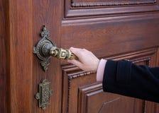 Een vrouwelijke hand die een krukas van een oude houten deur houden stock foto