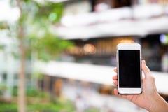Een vrouwelijke hand die mobiele telefoon houden royalty-vrije stock afbeelding