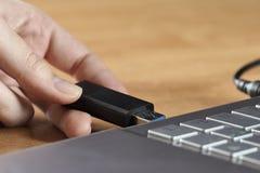 Een vrouwelijke hand die een USB-flitsaandrijving vóór laptop houden royalty-vrije stock foto's