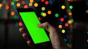 Een vrouwelijke hand gebruikt een smartphone met het groen scherm stock videobeelden