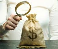 Een vrouwelijke hand houdt een vergrootglas over een geldzak met muntstukken Conceptenanalyse van winsten en inkomens Begroting p royalty-vrije stock foto