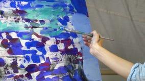 Een vrouwelijke hand maakt keurige vlekken met zwarte olieverf over het canvas, een beetje langzame motie stock video