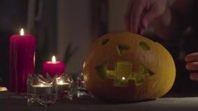 Een vrouwelijke hand plaatst een kaars in hefboom-O '- lantaarn stock footage