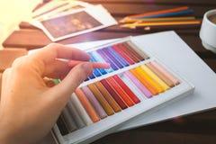 Een vrouwelijke hand trekt pastelkleur op een wit blad, op een donkere lijst is een kop van koffie Stock Foto