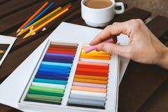 Een vrouwelijke hand trekt pastelkleur op een wit blad, op een donkere lijst is een kop van koffie Stock Foto's