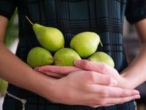 Een vrouwelijke holding verscheidene peren stock fotografie