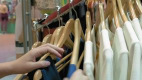 Een vrouwelijke klant doorbladert de doeken stock footage