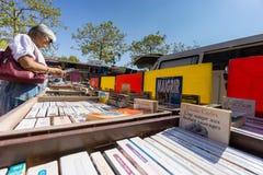 Een vrouwelijke klant leest een openlucht gebruikt boekenstalletje in Cogolin, Var, Frankrijk door Stock Fotografie