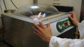 Een vrouwelijke kok die vacu5um sommige garnalenvleespennen voor de catering in Italië, 4K zetten stock videobeelden