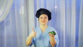 Een vrouwelijke kok glimlacht, houdt een avocado in haar hand en toont de klasse stock footage