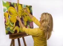 Een vrouwelijke kunstenaar die in haar studio schildert stock foto's