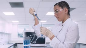 Een vrouwelijke laboratoriumtechnicus brengt een blauwe vloeibare steekproef naar een reageerbuis over gebruikend micropipette te stock video