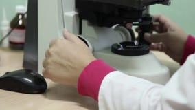 Een vrouwelijke laboratoriumtechnicus gebruikt een microscoop stock footage