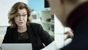 Een vrouwelijke manager legt nieuw projectplan aan collega's voor op vergadering, die idee?n op flipchart binnen verklaren aan me stock videobeelden