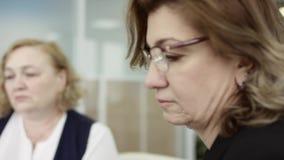 Een vrouwelijke manager legt nieuw projectplan aan collega's voor op vergadering, die idee?n op flipchart binnen verklaren aan me stock video