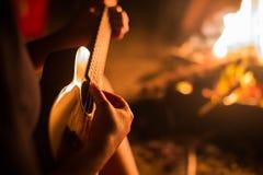 Een vrouwelijke musicus het spelen gitaar die buiten, naast een brand zitten Ontspanning royalty-vrije stock fotografie