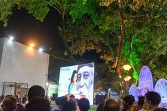 Een vrouwelijke omroeper wordt gezien in het grote scherm onder publiek, Rabindra Jayanti, Kolkata royalty-vrije stock afbeelding