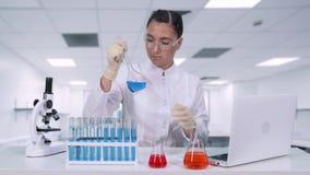 Een vrouwelijke onderzoeker analyseert de vloeistof in de fles en doet klinische proeven Een vrouwelijke wetenschapper leidt gene stock video