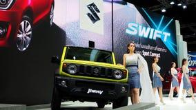 Een vrouwelijke presentator bevindt zich naast Suzuki Jimny royalty-vrije stock afbeelding