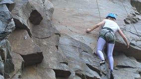 Een vrouwelijke rotsklimmer beklimt op een rots Het leren te beklimmen Rots, meisje, alpinisme stock videobeelden