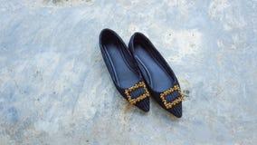 Een vrouwelijke schoen op de cementmuur stock afbeeldingen