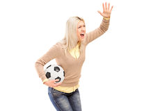 Een vrouwelijke sportventilator die een voetbal en het schreeuwen houden Stock Foto's