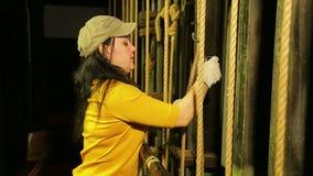 Een vrouwelijke stadiumarbeider in handschoenen klemt de kabel vast om het theatergordijn op te heffen stock video