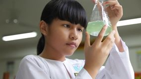 Een vrouwelijke student die een kegelfles houden stock videobeelden