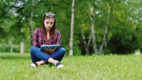 Een vrouwelijke student treft voor examens voorbereidingen Zit op een gazon in het park, geniet van een tablet stock videobeelden