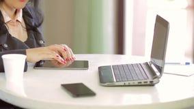 Een vrouwelijke student werkt aan laptop in een koffie en het doorbladeren beelden op een tablet Panorama van recht op lef stock footage