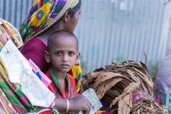Een vrouwelijke tabakslandbouwer en haar kind die naar markt gaan die aan droog tabaksblad verkopen stock foto