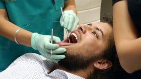 Een vrouwelijke tandarts die de tanden van een jonge mancontroleren stock footage