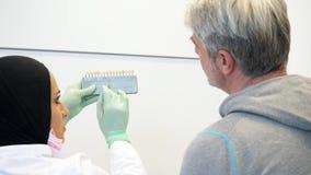 Een vrouwelijke tandarts die in hijab een patiënt raadplegen die de schaduw van tanden om kleurt te nemen stock footage
