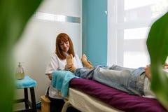 Een vrouwelijke therapeut behandelt de geduldige voeten van ` s stock foto