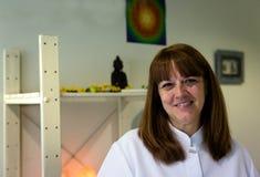 Een vrouwelijke therapeut die bij het overleg van een therapiecent glimlachen stock foto
