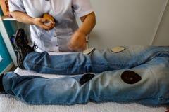 Een vrouwelijke therapeut doet magneettherapie op een patiënt stock fotografie