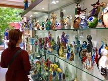Een vrouwelijke toerist die voor glasbeeldhouwwerken bij een winkel in Murano, Italië winkelen Murano is beroemd voor zijn Veneti royalty-vrije stock foto