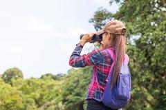 Een vrouwelijke toerist zit op rots gebruiken verrekijkers te zien zijn stock foto's