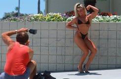Een vrouwelijke verbuiging van de lichaamsbouwer voor de camera, Stock Foto's