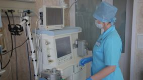 Een vrouwelijke verpleegster bereidt een elektronisch innovatief medisch hulpmiddel voor chirurgische operatie voor Nieuwe medisc stock video