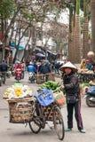 Een vrouwelijke Vietnamese straatventer met oude fiets en vruchten op de bamboemanden op Lao Kai-straat, grens Vietnam-China royalty-vrije stock foto
