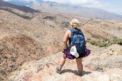 Een vrouwelijke wandelaar, die in de Indische Canions in Palm Springs Californië op een klip wandelen stock foto